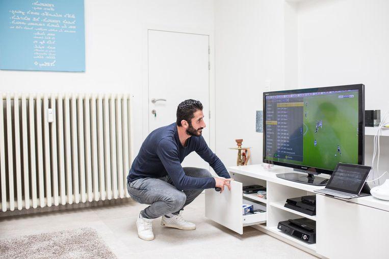 Malki zoekt donderdag de juiste tv-zender voor Syrië - Australië (1-1). Beeld John van Hamond / de Volkskrant