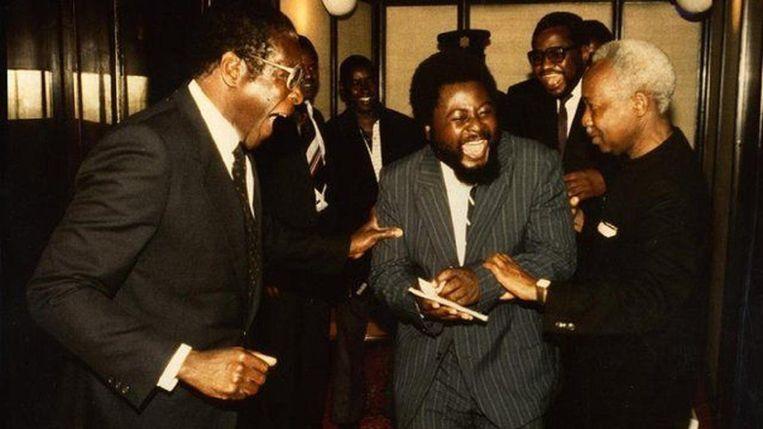 Betere tijden in de jaren tachtig: Robert Mugabe en journalist Wilf Mbanga lachen om een grapje van Julius Nyerere, president van Tanzania. Mbanga werd later een van scherpste critici van Mugabe met zijn krant The Zimbabwean. Beeld bbc