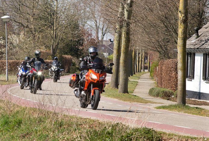 Op gepaste afstand op de motor door de bocht bij Beek.