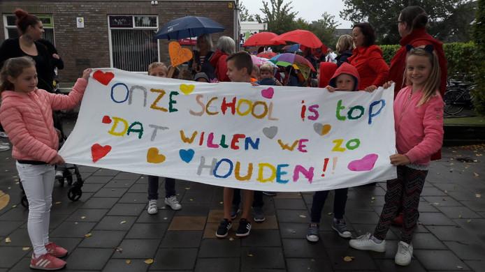 Leerlingen van de Kohnstammschool voeren een spandoek mee.