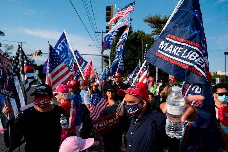 Terwijl Donald Trump er wegens coronabesmetting opgenomen is, verzamelen zijn aanhangers zich voor het Walter Reed Medical Center (in Bethesda, Maryland). Beeld AFP