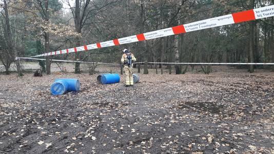 Een brandweerman onderzoekt gedumpte vaten in Wageningen.