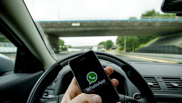 Een automobilist verstuurt een bericht via WhatsApp. Beeld null