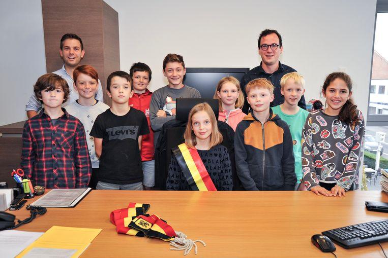 De leden van de kindergemeenteraad met burgemeester Jelle Wouters en voorzitter van de gemeenteraad Bart De Vos