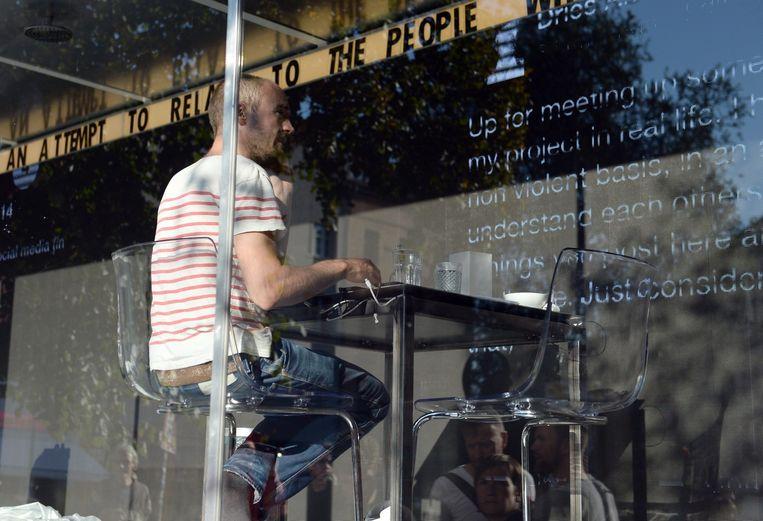 Kunstenaar Dries Verhoeven zit in een glazen container in Berlijn. Tijdens deze openbare voorstelling worden de chatgesprekken die hij voert via datingsites op een scherm getoond. Beeld ANP