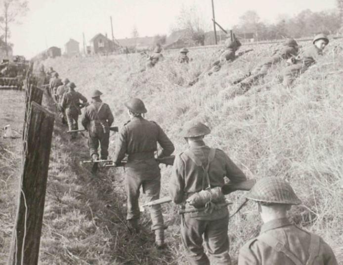 Britse militairen lopen langs het spoor in Rosmalen. Op de achtergrond het station en de Rode Kruistrein.