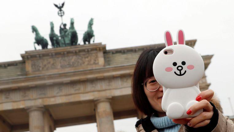 Een Chinese tourist aan de Brandenburger Tor.