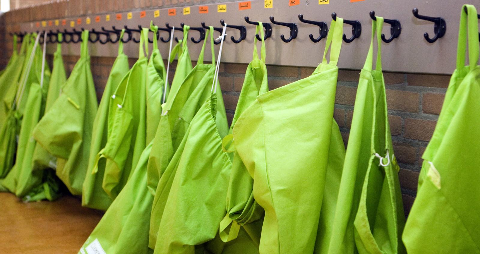 Luizenzakken aan de kapstok van een basisschool. De kinderen moeten hier hun jassen in doen tijdens de les om verspreiding van hoofdluis te voorkomen.