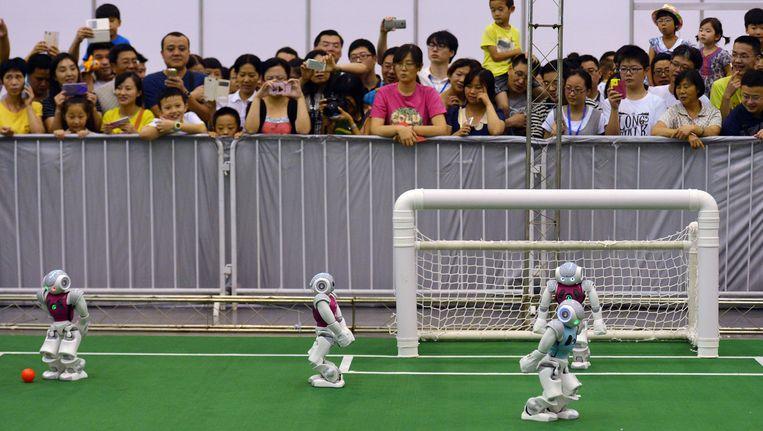 Het publiek kijkt naar de voetballende robots op de RoboCup 2015 Beeld ap