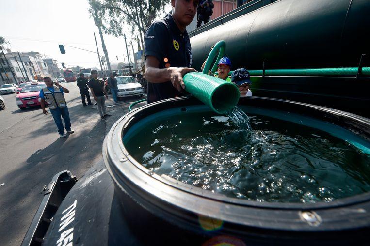 Vanwege het onderhoud aan de waterleidingen in Mexico-Stad zet staatswaterbedrijf Conagua honderden tankwagens in om watertanks te vullen in deelgemeentes als Iztapalapa en Tláhuac. Beeld AFP