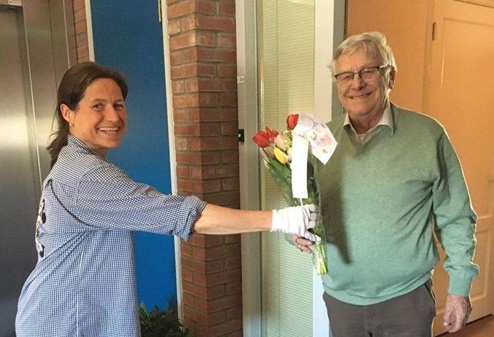 Kirsten de Kluijs overhandigt een bloemetje aan een Oisterwijker