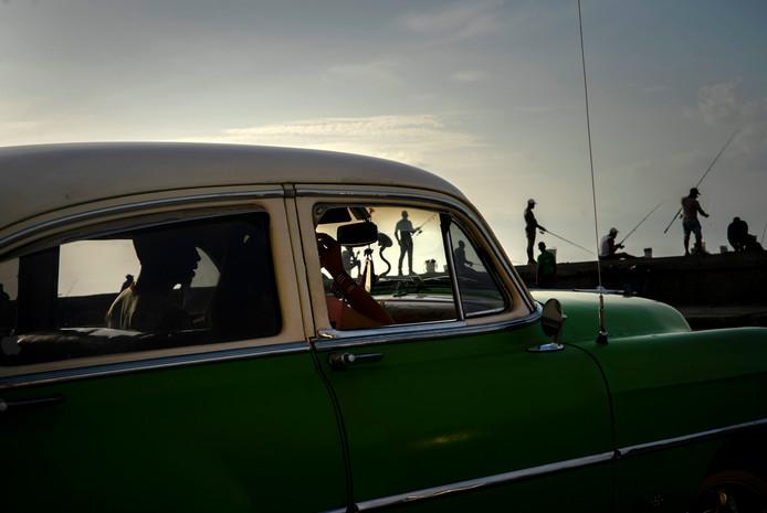Een auto rijdt langs vissers in Havana.