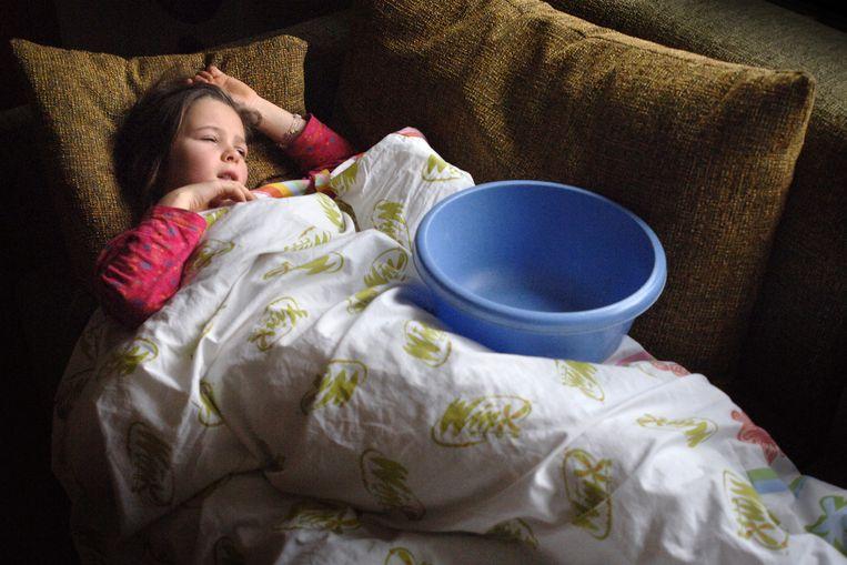 Een kind ligt ziek met griep op de bank. Door de coronamaatregelen zal het griepseizoen dit jaar waarschijnlijk meevallen. Beeld Marcel van den Bergh