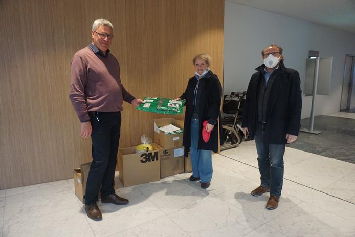 Minou Esquenet (midden) overhandigt het pakket aan directeur Hans Rigauts (links).