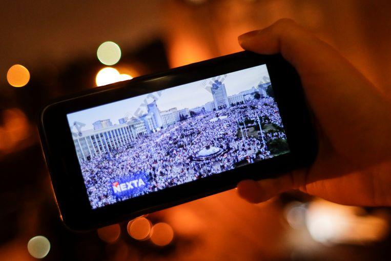 Een man kijkt op 19 augustus 2020 via het Telegram-kanaal Nexta Live naar de protesten in Minsk, Wit-Rusland. Beeld AP