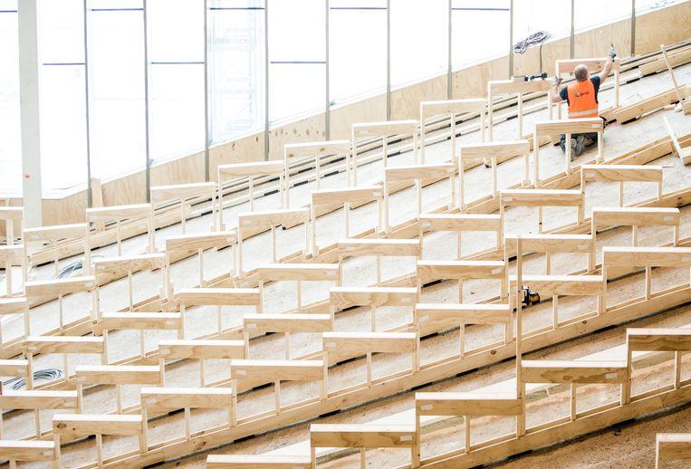 Een bouwvakker aan het werk in de grote collegezaal. Het voormalig ministerie van Binnenlandse Zaken in Den Haag wordt omgebouwd tot universiteit. Beeld Freek van den Bergh / de Volkskrant
