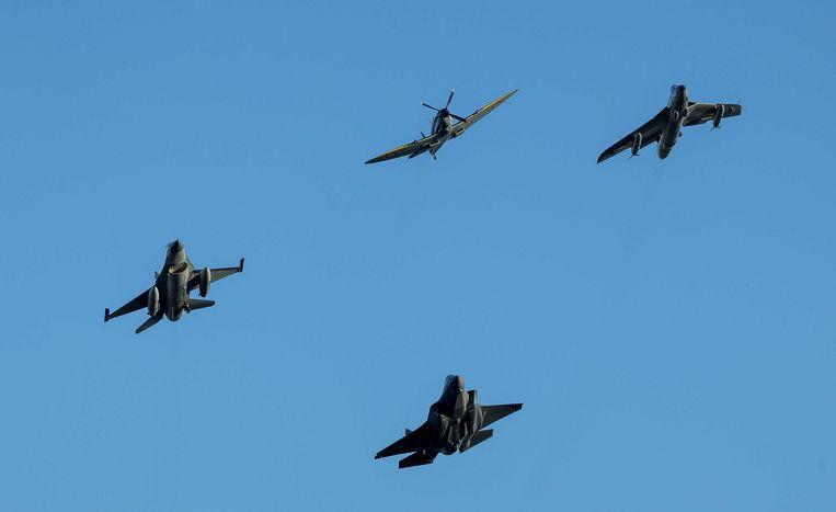 De eerste F-35, ook wel bekend als de Joint Strike Fighter, komt aan op de vliegbasis Leeuwarden, vergezeld van oudere Nederlandse militaire vliegtuigen:  een F-16, een oudere Hawker Hunter en een stokoude Spitfire. Beeld ANP