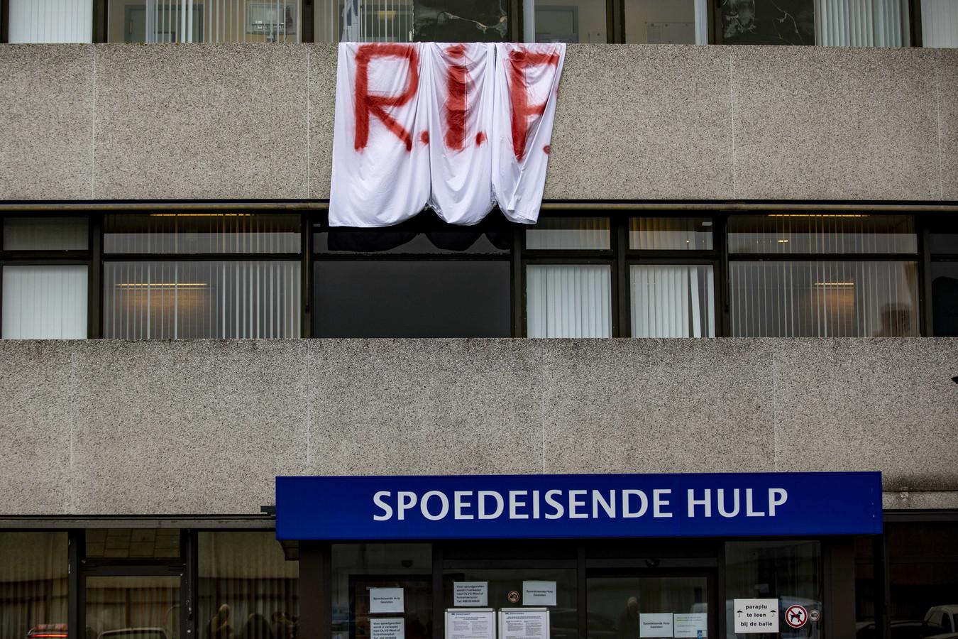 Aan de gevel van het ziekenhuis hangt een spandoek. Rest In Peace.