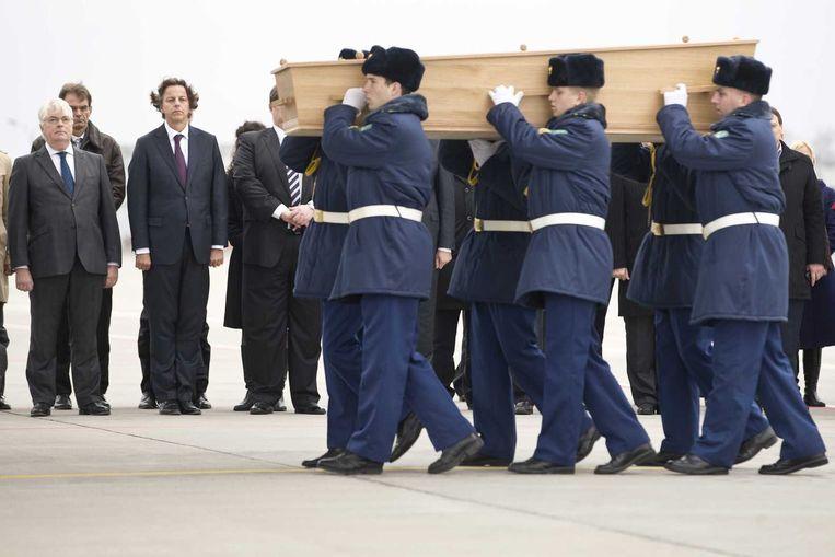 Een kist met stoffelijke resten van slachtoffers van MH17 wordt op de luchthaven van Charkov in een Hercules-transportvliegtuig van de Koninklijke Luchtmacht gedragen. In totaal vijf kisten zullen naar Eindhoven worden gevlogen. Bij de ceremonie is ook minister Bert Koenders (2de L) van Buitenlandse Zaken. Beeld anp