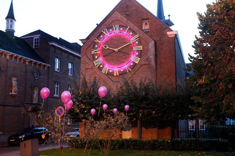 Het torenuurwerk van de bibliotheek kleurt fel roze om aandacht te vragen voor borstkanker.