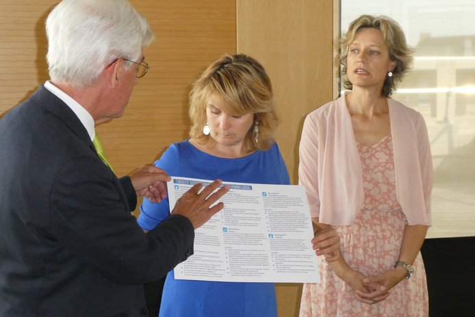 Burgemeester Jan Pommer (links) en Karin van Esch, directeur publieke gezondheid GGD bieden burgemeester Marieke Moorman van Bernheze de leidraad met checklist aan voor de aanpak van verwarde mensen. Moorman is voorzitter van de Vereniging Brabantse Gemeenten.