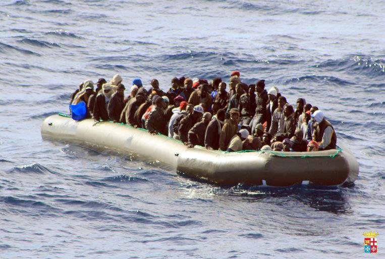 Screenshot van een video die is gemaakt vanaf een marineschip. De rubberboot zit vol met vluchtelingen. Beeld EPA
