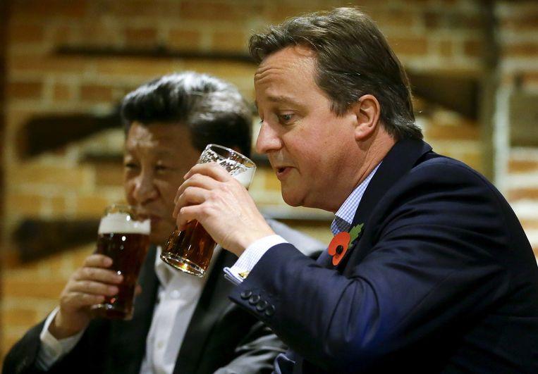 De Engelse premier David Cameron drinkt een biertje met de Chinese president Xi Jinping tijdens diens staatsbezoek aan Groot Brittannië in oktober. Beeld reuters