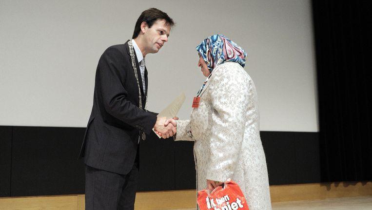 Een Marokkaanse krijgt het Certificaat van Nederlanderschap. Beeld Joost van den Broek / de Volkskrant