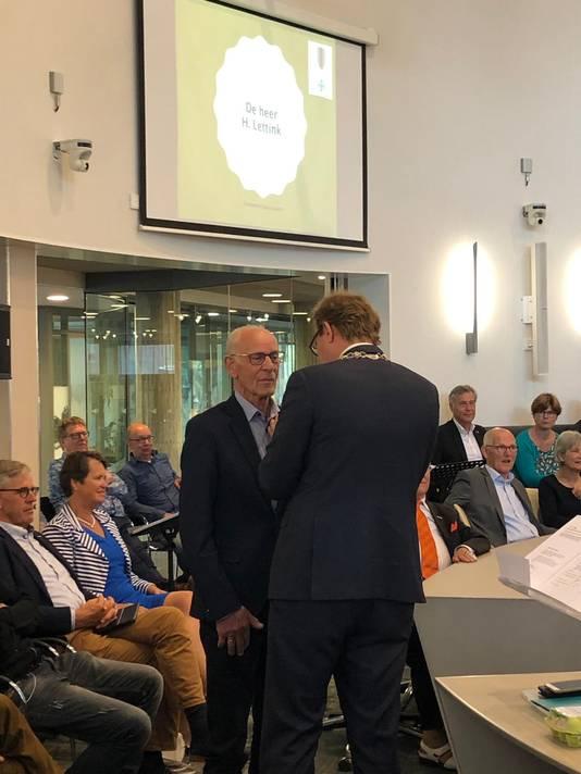 Herman Lettink krijgt een lintje opgespeld door burgemeester Mark Boumans.