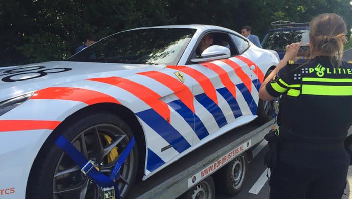 De auto-ambulance met daarop de Ferrari werd gestopt op de Pleyroute door agenten. Die gingen er meteen mee op de foto.