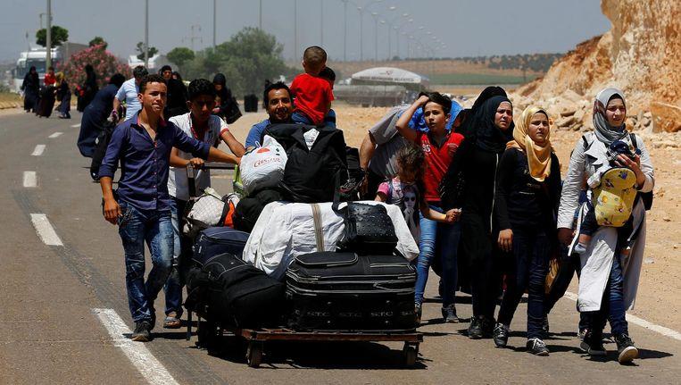 Syriërs onderweg van Turkije naar Syrië. Beeld reuters