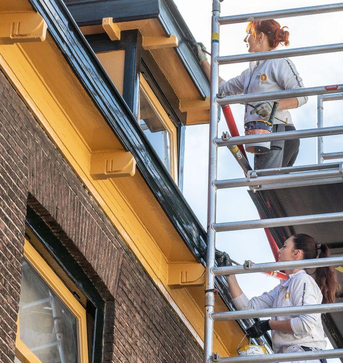 Lydia (boven) en Pamela bezig met een klus aan het Diezerplein in Zwolle bij Stef Mulder bloemist.