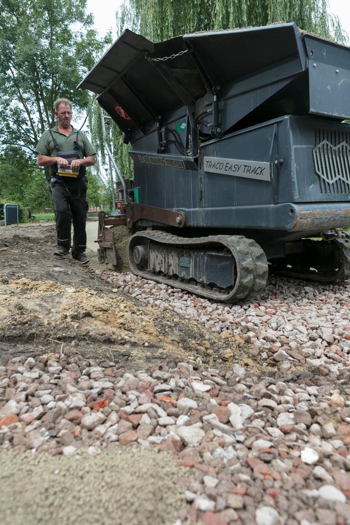 Martin Potjes legt met een eigen op afstand bestuurbaar grindkiep-machine de paden in het nieuwe centrumpark van Boxtel aan.