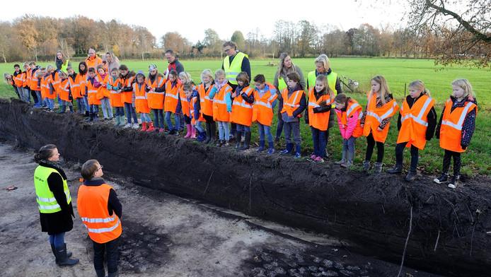 Archeologen geven in de sleuf uitleg aan leerlingen van De Hoeksteen.