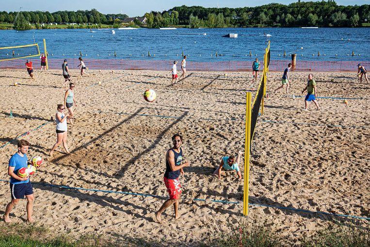 Beachvolleyballers oefenen bij Laagravenseplas op de eerste tropische dag van 2020. De mensen houden zich nog steeds aan de coronaregels maar steeds iets losser. Beeld Guus Dubbelman / de Volkskrant