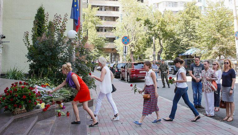 Mensen leggen bloemen voor de Franse ambassade in Kiev. Beeld epa