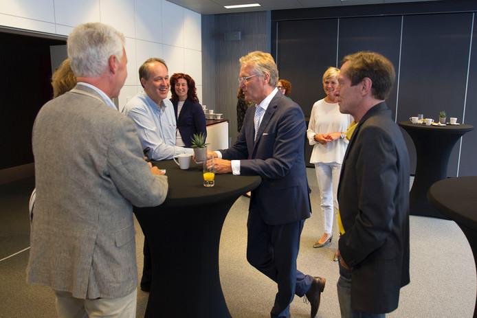 John Jorritsma in gesprek met een aantal leden van het Eindhovense college en de gemeenteraad. Op de achtergrond (in het wit gekleed) Georgette Jorritsma.