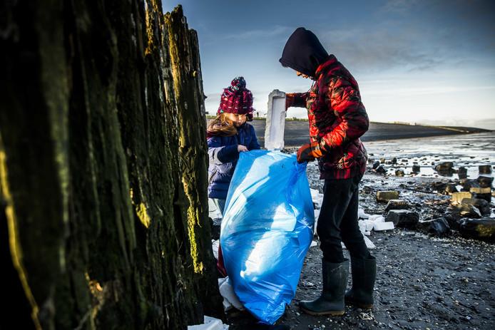 Vrijwilligers ruimen de troep op die op de Waddendijk is terechtgekomen nadat een vrachtschip 270 containers was verloren.
