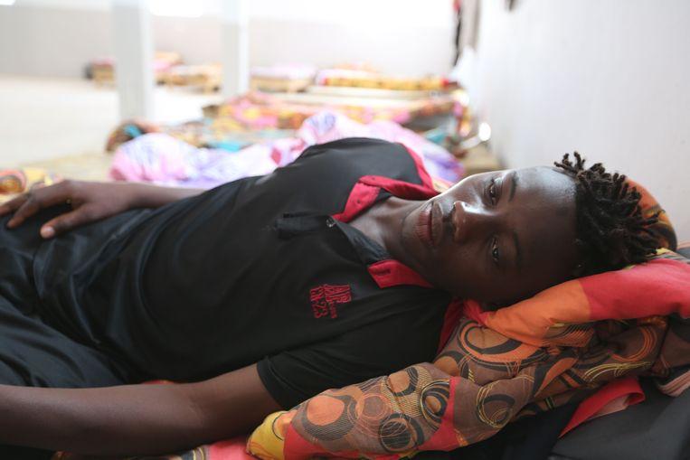 Een migrant uit Mali, Souleyman Coulibaly, die is gered nadat de boot omsloeg, ligt op een bed bij het Red Crescent centrum in de Tunesische kustplaats Zarzis, 4 juli, 2019. Beeld AFP