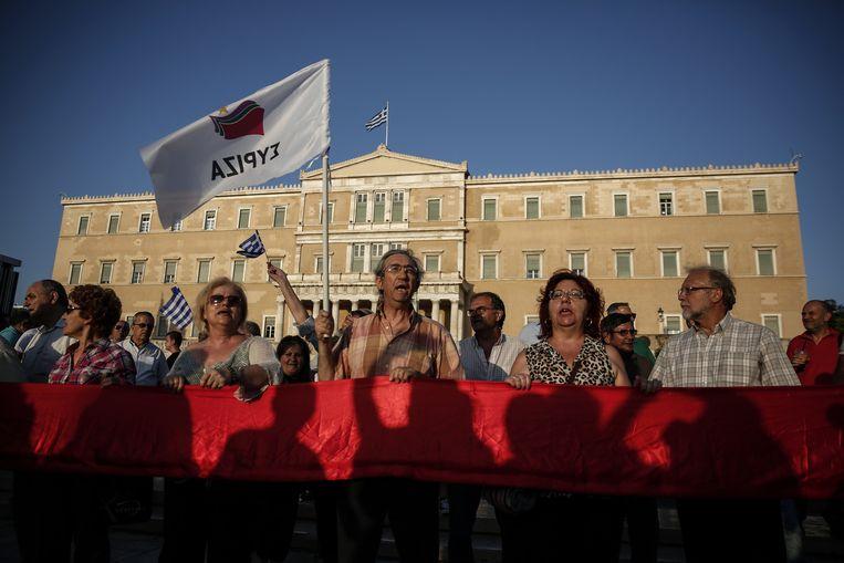 Aanhangers van de Griekse regeringspartij Syriza voor het parlement in Athene. Beeld ap