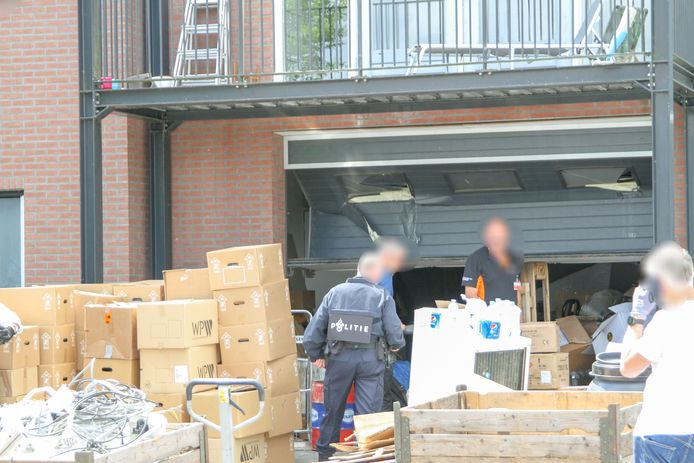 Grote hoeveelheden materiaal - waarschijnlijk bedoeld voor hennepkwekerijen - worden naar buiten gereden en in een vrachtwagen afgevoerd in Ede.