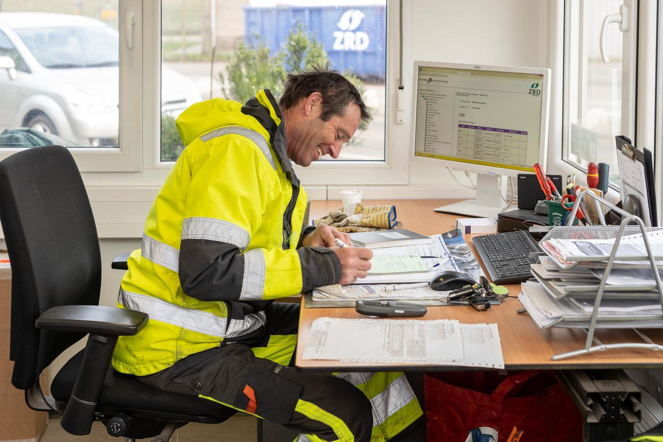 Charles van de Bilt schrijft een bonnetje uit voor een klant die asbest komt brengen. Die mag de partij ook gelijk bij hem afrekenen.