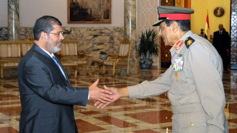 De Egyptische president Morsi schudt de hand van Tantawi. Beeld epa
