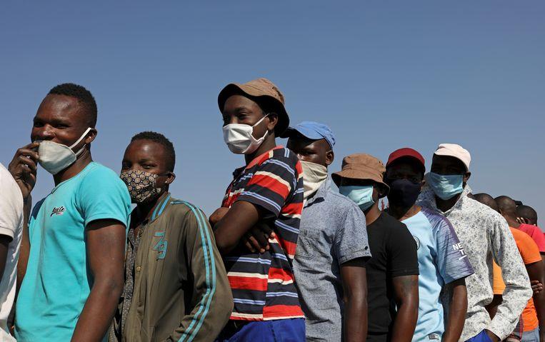 Mensen dragen mondmaskers in de rij voor eten.   Beeld Reuters