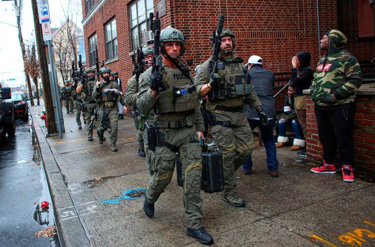 Zwaarbewapende troepen rukken uit bij de schietpartij in Jersey City. Beeld AFP