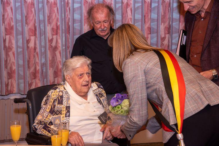 Martha Plaetinck wordt 100 en krijgt bloemen en gelukwensen van burgemeester Elsie Sierens en schepen Renaat De Sutter.