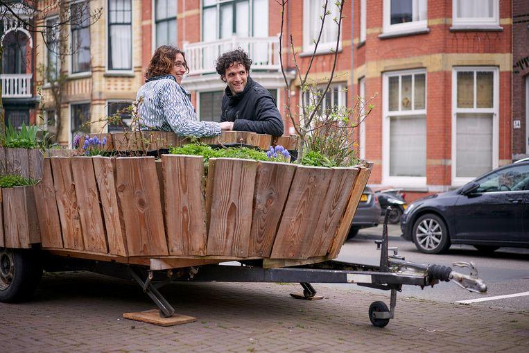 Walter Dresscher van De Natuurlijke Stad in gesprek met Sandra Nap in de DebatMobiel, een mobiele plek met een tuintje om samen met bewoners te praten over het project Vrijstraat. Beeld Phil Nijhuis