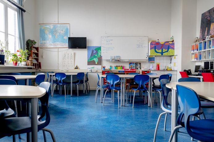 Stoelen en tafels in een klaslokaal op een basisschool.