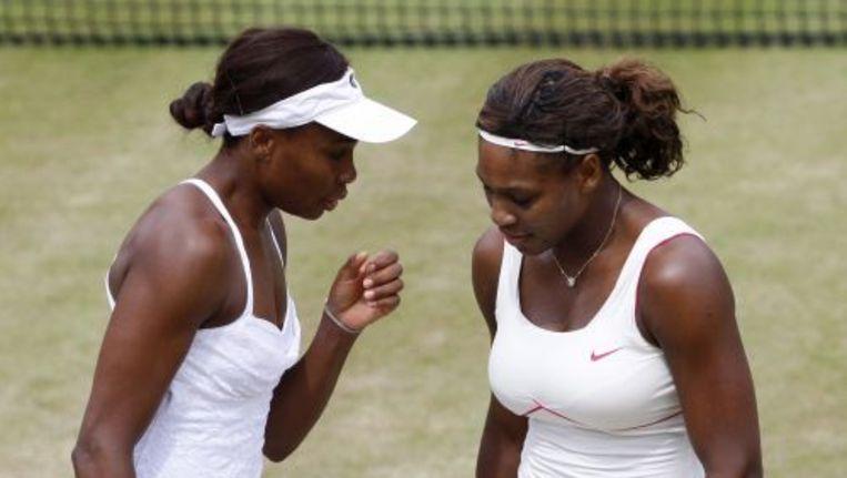 Venus (L) en Serena Williams tijdens de halve finales van het vrouwendubbelspel op Wimbledon. Foto ANP Beeld