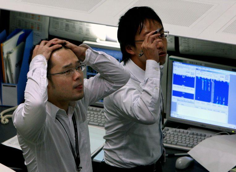 Handelaren op de beurs van Tokio zien vrijdag vol ongeloof hoe de koersen onderuit gaan.  Beeld AP
